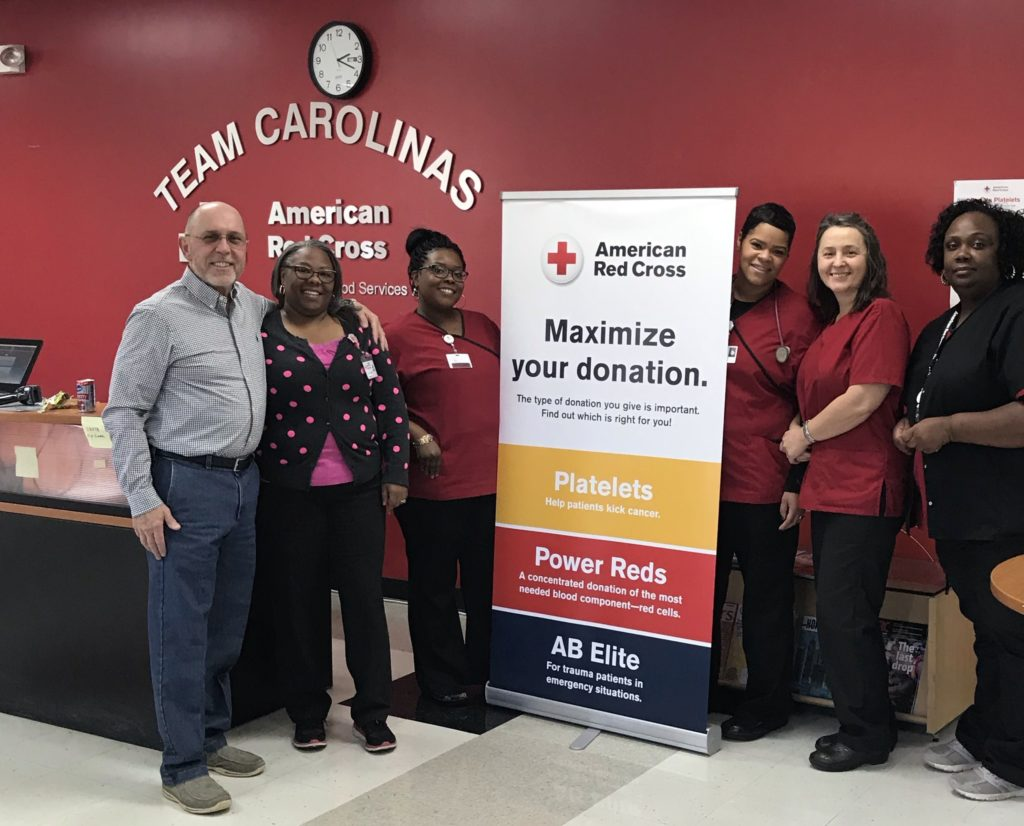 Kirk Davis standing with phlebotomists at a blood center in North Carolina.