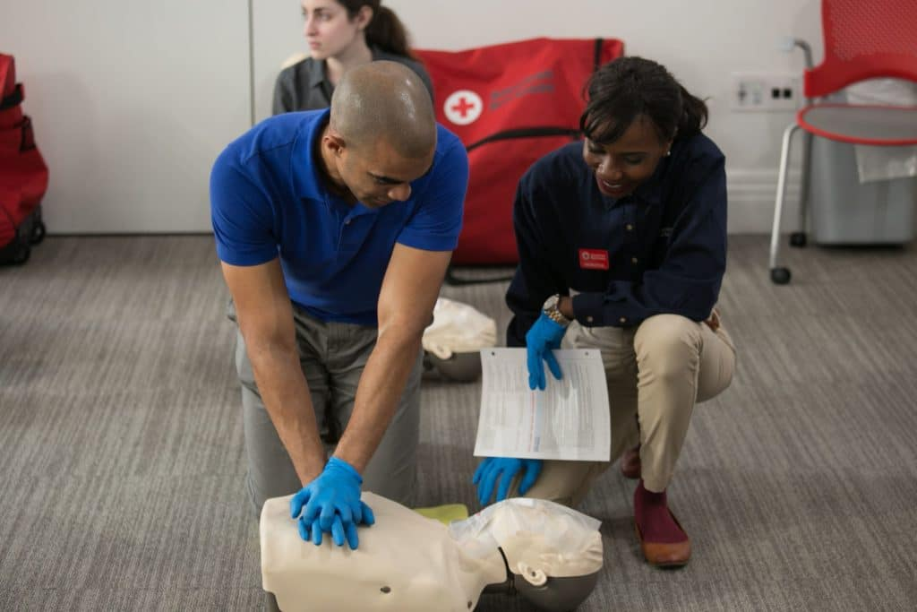 An instructor teaching CPR. The trainee is practicing compressions on a manikin.