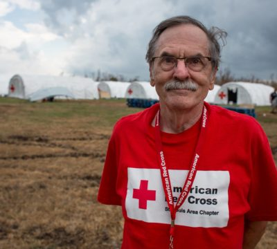 Red Cross disaster relief worker standing in front of Red Cross tent camp for relief workers in Big Pine Key, Florida.