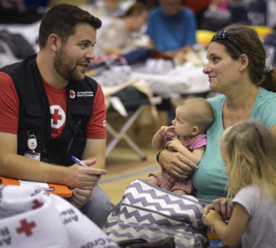 A red cross volunteer sitting with a shelter resident and her family.
